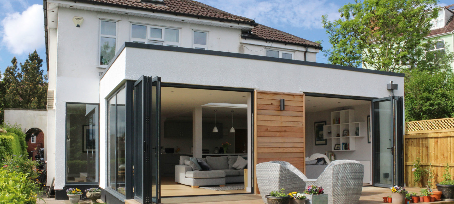 Modern extension from garden showing decking and sliding doors