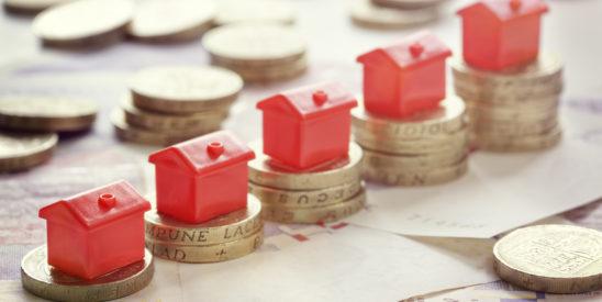 mini houses on stacks of pound coins